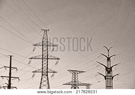Several High metal towers. Power line with conductors against the sky, vintage toned photo. City, industrial district poster