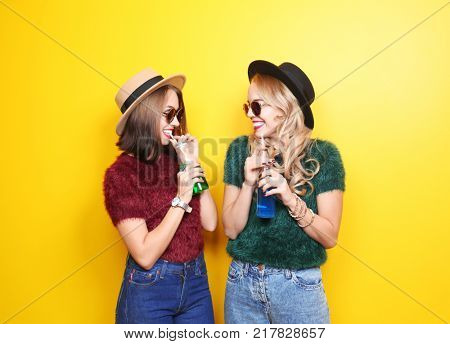 Two happy hipster girls with drinks on color background