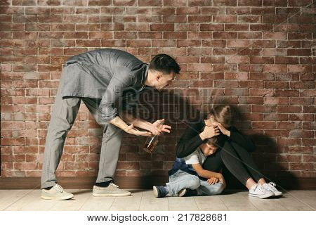 Drunk man threatening his wife and son against brick wall