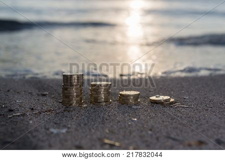 Pile of New British Pound Coins on the sand. New Pounds in a Warm Sunrise Light.