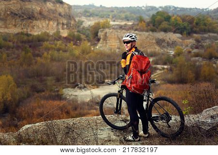 Side view of man in sportswear on mountain bicycle on background of landscape.
