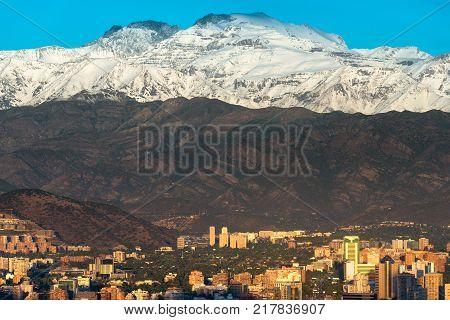 Buildings at Las Condes district in Santiago de Chile and Los Andes mountain range.