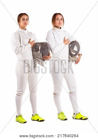 Two European young girls are sportsmen, fencers, dressed in a fencing uniform, with one hand holding a mask for fencing and a second hand on the heart. Isolated on white background.