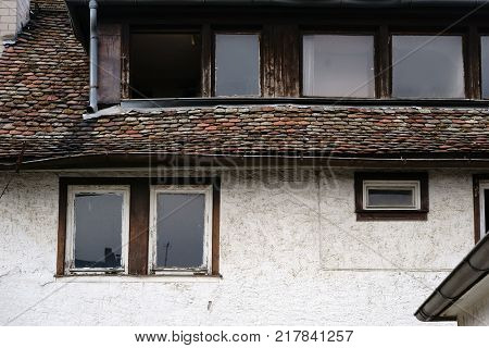 Leaning dilapidated and nostalgic windows and roof shingles of an old and listed building.