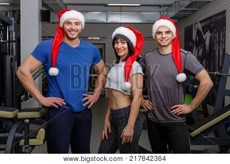 A group of happy young athletes, dressed in red Santa's caps with a fur pom-pon, stand next to each other and smile sweetly. Indoors in the gym.