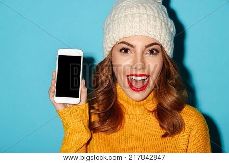 Close up portrait of a happy young girl dressed in winter clothes showing blank screen mobile phone and looking at camera isolated over blue background