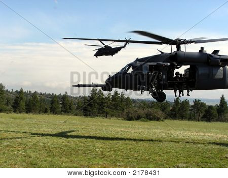 A US Air Force MH-60 Pavehawk takes off while in the background a MH-53 turns away from the Landing Zone after taking off. poster