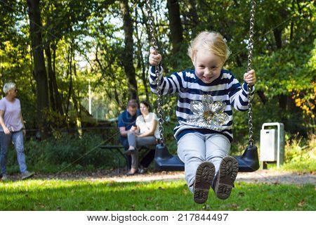 children having fun swinging on a swing.