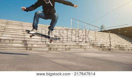 Skateboarder jumping on city stairs with skateboard