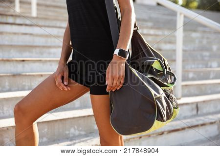 Close up of a woman dressed in sportswear carrying bag while walking up the stairs outdoors