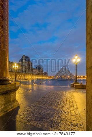 PARIS, FRANCE - DECEMBER 04, 2017: View of famous Louvre Museum with Louvre Pyramid at night. Louvre Museum is one of the largest and most visited museums worldwide