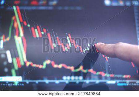 Finger pointing on stock exchange market chart