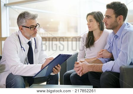 Couple meeting medical specialist at hospital