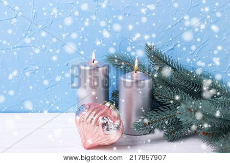 Christmas background. Silver candles branches fur tree and and pink toy on white background against blue wall. Selective focus is on candles. Drawn snow.