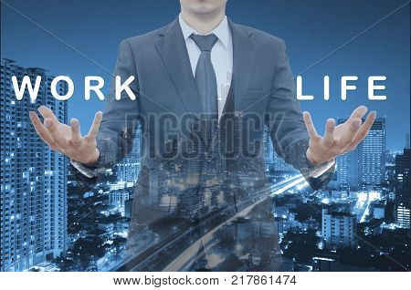 Double exposure of professional businessman hold work and life texts balance on 2 hands with cityscape blue cool tone background in work & life balance concept