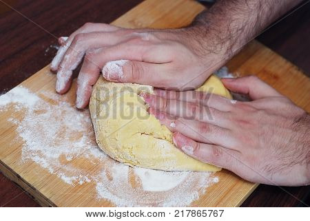 Mens Hands Kneading Bread Dough on a