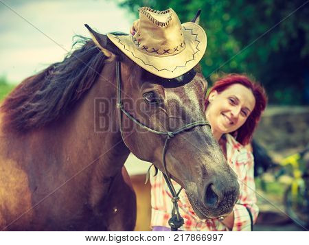 Fun with animals concept. Western redhead woman hugging horse wearing cowboy hat