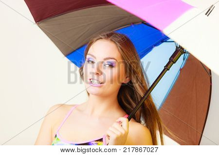 Woman cheerful summer girl standing under colorful rainbow umbrella Attractive female long hair model. Forecasting and weather season concept