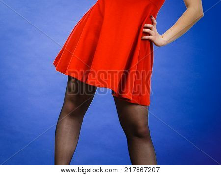 Woman wearing red dress or skirt and dark tights Studio shot on blue background.