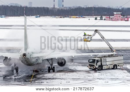 Ground crew provides de icing. They are spraying the aircraft, which prevents the occurrence of frost.