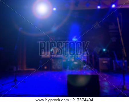 De-focused concert stage with laser lights and beams.