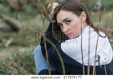 Portrait of a woman in white shirt, sitting with the back to the camera, looking back. Autumn forest.
