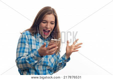 Happy young woman in blue plaid shirt holding smartphone in hands and looking at the screen. Atractive positive female standing and posing over white background.