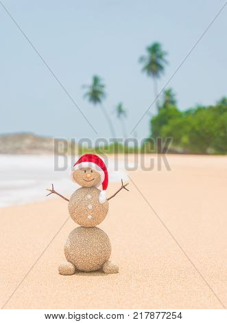 Christmas sandy snowman in red santa hat at tropical ocean palm beach. Holiday concept for New Year Greeting Cards and traveling in hot countries destinations.
