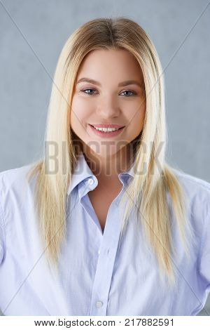 Portrait of a sexy woman in a man's shirt wearing on a gray background looks at the camera and smiling look advice to give wants objections are not accepted.