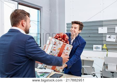 Attractive man smiling and giving xmas presents to colleaguaes. Smilling people celebrating Christmas with gift boxes. Close-up of human. Holiday concept.