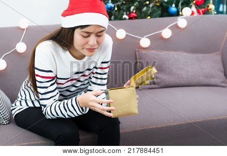 Asian woman upset when open gold xmas gift box at holiday party on sofa boredom Christmas party present