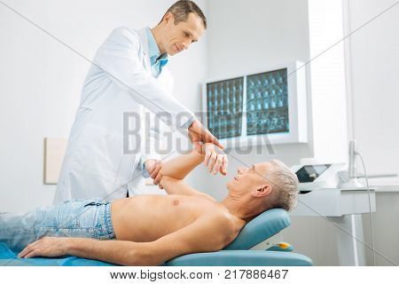 At the hospital. Nice serious male doctor standing near his patient and doing a medical checkup while working in the hospital