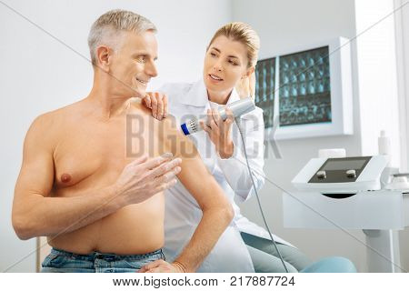 Concern about health. Delighted positive aged man sitting on the bed and asking a question to his doctor while being examined