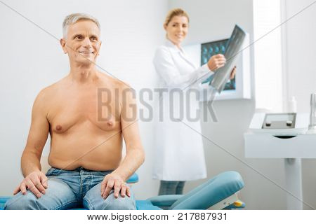 Optimistic attitude. Joyful delighted senior man sitting on the medical bed and smiling while being in the positive mood