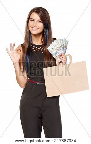Cash payment approved. Smiling woman holding paper shopping bag with blank copy space for text and cash US dollars while gesturing OK, over white background