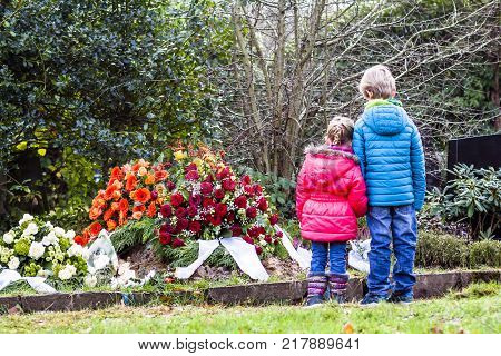 Little brother and sister standing at the grave of their parents in the graveyard