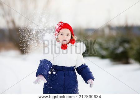 Cute toddler girl outdoors on a sunny snowy day walking playing snowballs having fun winter activity for kids.