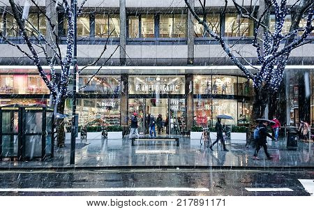LONDON UK - 11 DECEMBER 2017: A busy London street scene with Christmas shoppers making their way past the facade and entrance to the Planet Organic shop on Tottenham Court Road on a cold and snowing winters day.