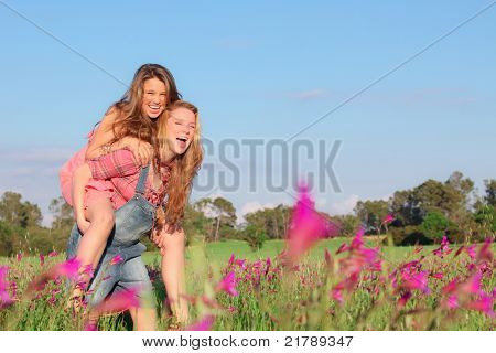 happy smiling spring or summer piggy back teens or teenager kids
