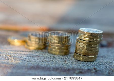 Picture of four piles British pound coins. UK Money New Pounds in a Warm Light.
