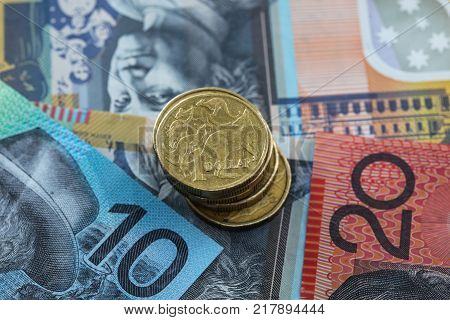 A stack of Australian Dollar Coins placed on top of ten - twenty and fifty dollar notes.