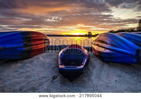 Outdoor Lifestyle. Kayaks line a sandy Lake Michigan beach as the sunrise over the horizon in Traverse City, Michigan, USA.