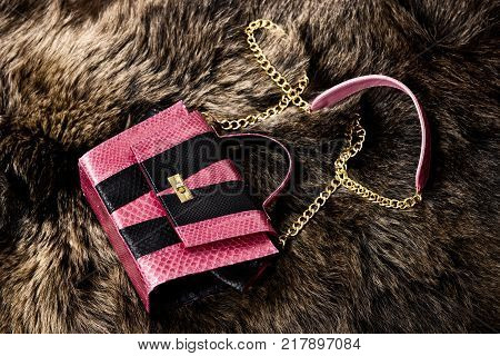 Pink leather bag on a bear's fur. Fashion concept.