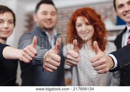 Team holding thumbs up. Close-up of business team holding their thumbs up. Four hands showing thumbs up against the backdrop of the office, two men and two women.