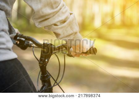 Woman riding a mountain bicycle along path at the forest. Closeup on handlebar with female hand. Healthy lifestyle and sport concept
