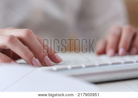Female hands typing on silver keyboard using computer pc at workplace closeup. White collar job digital shopping office lifestyle search success enter login password and credentials concept
