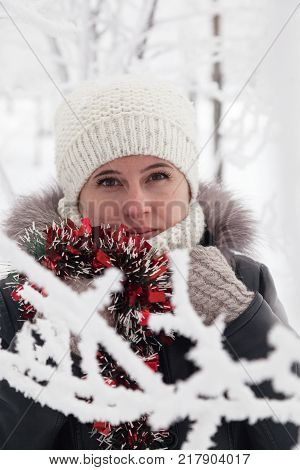 The portrait of the frozen woman in a winter knitted white cap a winter jacket mittens keeps hands with a New Year's toy at a neck in the park in the snow winter