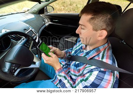 Young man driver using smart phone in car. Driver sitting in car and holding mobile smart phone with isolated screen. Modern smartphone with blank screen copy space for text or design