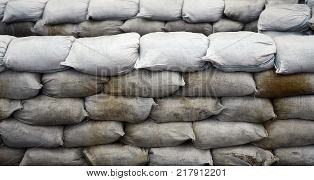 Background of many dirty sand bags for flood defense. Protective sandbag barricade for military use. Handsome tactical bunker