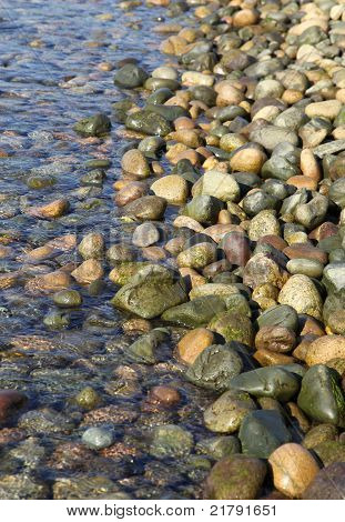 Water Rolling Gently Over Rocks On A Rocky Beach